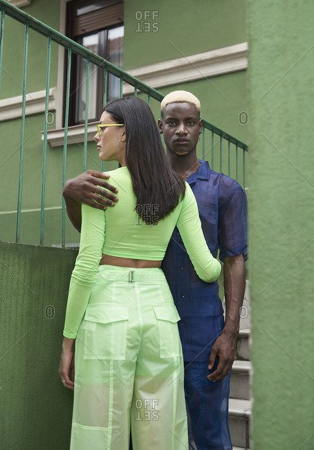 Stylish multiracial couple of models embracing each other while standing near green building in city