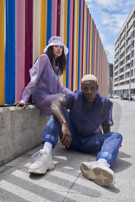 Emotionless multiethnic couple of models in trendy outfit sitting on street in city and looking at camera