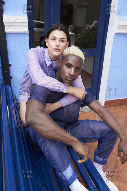 High angle of stylish multiracial couple sitting on bench in city and embracing while looking at camera