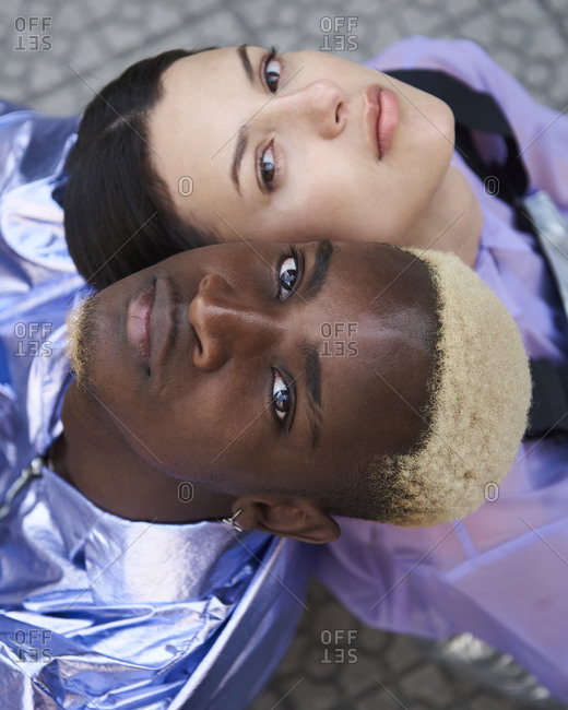 From above of carefree multiracial couple in trendy clothes touching heads gently while sitting on street and looking at camera