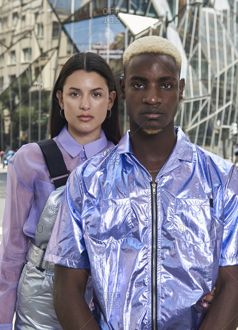 Low angle side view of multiracial couple in holographic clothes standing in city on background of futuristic glass building