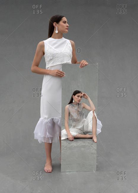 Calm women in white wear reflecting in mirror in studio on gray background