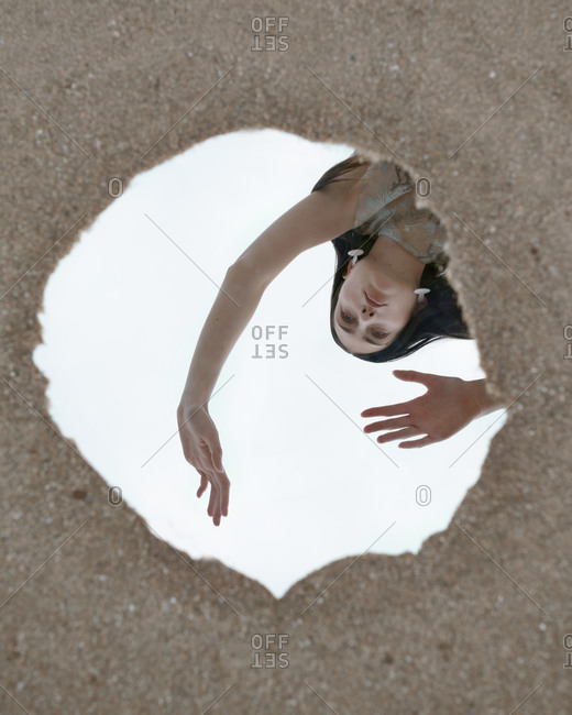 From above of emotionless female model with outstretched arms reflecting in mirror placed on ground and looking away