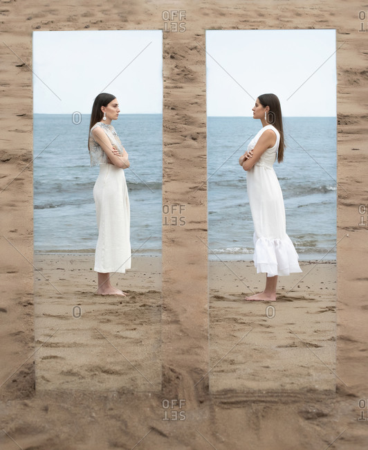 Side view of emotionless females in dresses standing with folded arms on sandy shore and looking at each other while reflecting in mirror on background of seascape