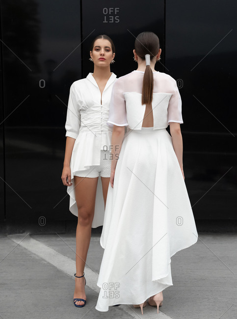 Unemotional female models wearing white trendy dresses and high heels standing near black building