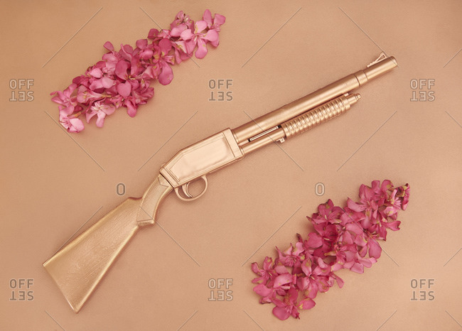 Top view of golden shotgun placed with flower petals on pink background in studio