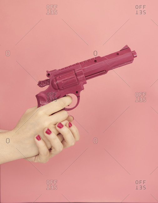 Unrecognizable female with manicure and plastic pistol on pink background in modern studio