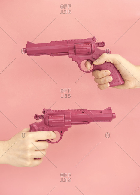 Unrecognizable people with manicure and plastic pistol on pink background in modern studio