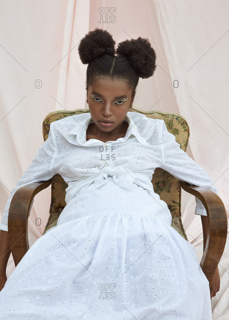 Serious fashionable female teenager with makeup and ponytails wearing white dress sitting in vintage armchair against white curtain