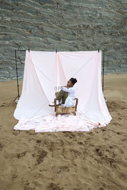Full body side view of African American female teen model in stylish outfit sitting on vintage chair placed against white curtain on sandy beach