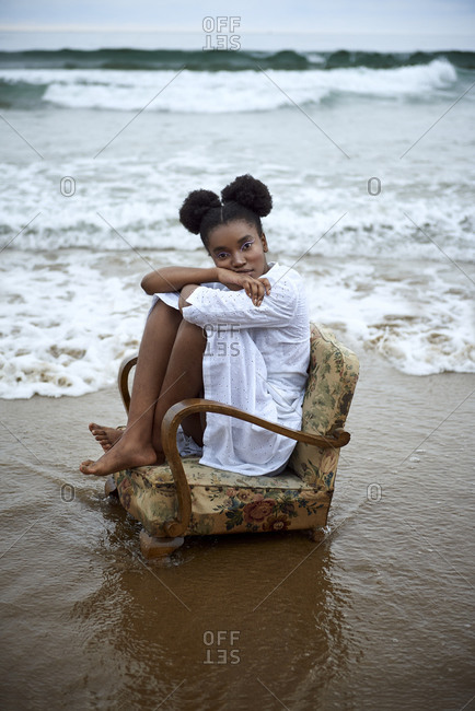 Full body side view of sad pensive barefoot teen female in white clothes sitting on vintage armchair placed on wet sand near waving sea
