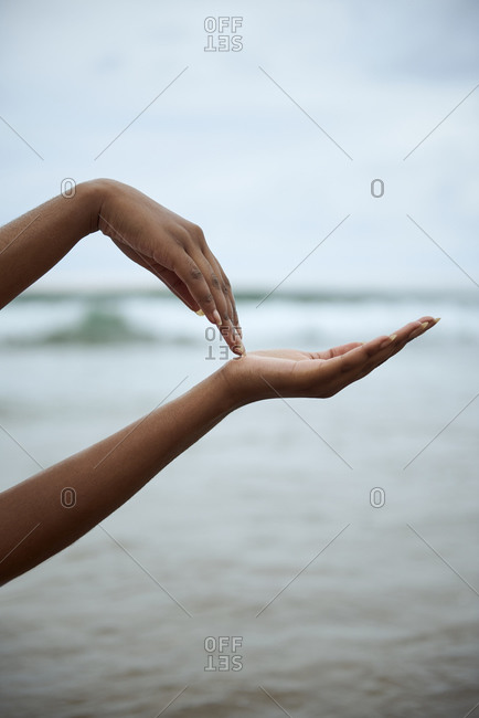 Crop anonymous black female keeping hands against blurred sea water while standing on beach in summer day