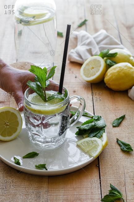 Crop unrecognizable person taking glass cup of tasty cold lemonade with soda water and mint leaves placed on wooden table