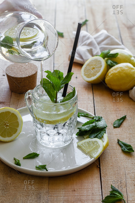 Cold refreshing drink with soda water and lemon garnished with fresh mint leaves served on glass cup with straw on wooden table