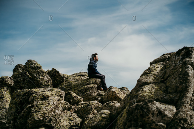 Side view of man sitting on the edge of on stone with eyes closed admiring Puerto de la Morcuera mountain range on cloudy day in Spain