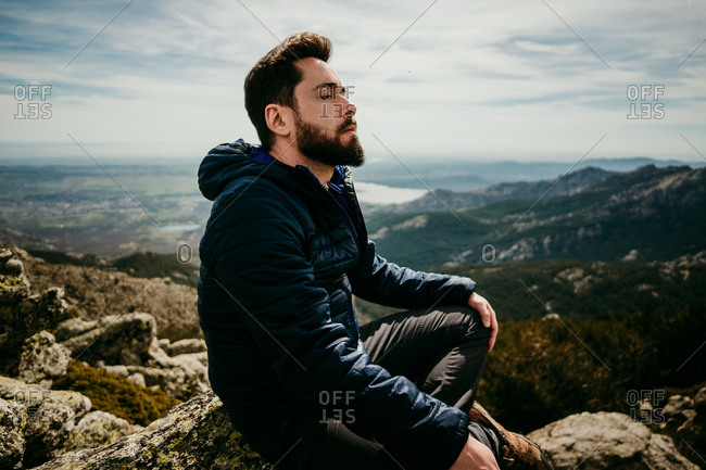 Side view of bearded male traveler sitting cross legged on rock and meditating with closed eyes against cloudy sky in Puerto de la Morcuera mountains in Spain