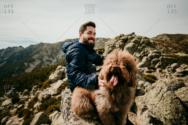 Cheerful bearded man sitting on stone near cute Labradoodle against overcast sky during trip in Puerto de la Morcuera mountains in Spain looking at camera