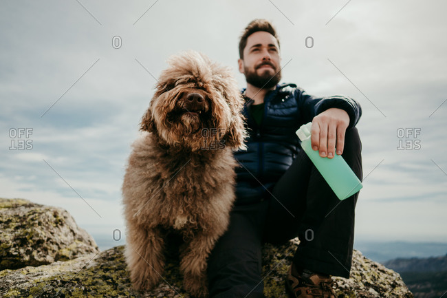 From below bearded man with bottle of water sitting on stone near cute Labradoodle against overcast sky during trip in Puerto de la Morcuera mountains in Spain