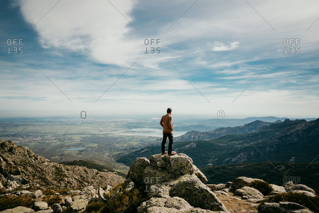 Back view of anonymous man with hands in pockets standing on stone and admiring Puerto de la Morcuera mountain range on cloudy day in Spain