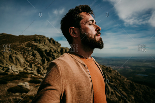 Side view of man standing on stone with eyes closed admiring Puerto de la Morcuera mountain range on cloudy day in Spain