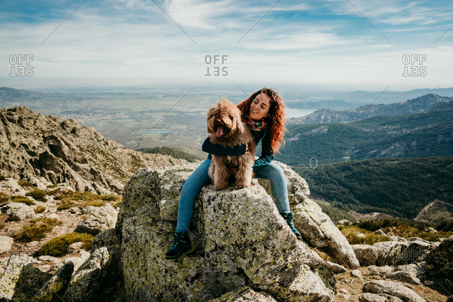 Full length female owner embracing fluffy Labradoodle while sitting on stone against cloudy sky in Puerto de la Morcuera mountains in Spain