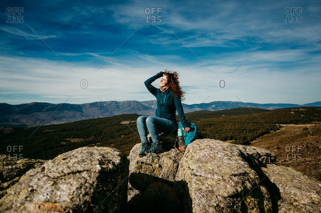 Optimistic woman smiling resting sitting on stones near backpack while traveling through Puerto de la Morcuera mountains on cloudy day in Spain