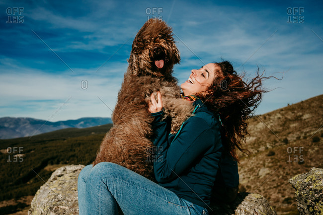 Side view of cheerful female owner laughing and playing with cute Labradoodle while resting in Puerto de la Morcuera mountains against cloudy sky in Spain