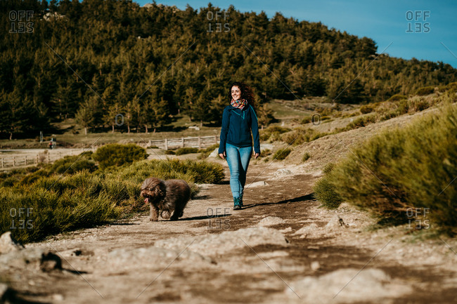 Happy female smiling and following fluffy Labradoodle while walking along path on sunny day in Puerto de la Morcuera mountains in Spain