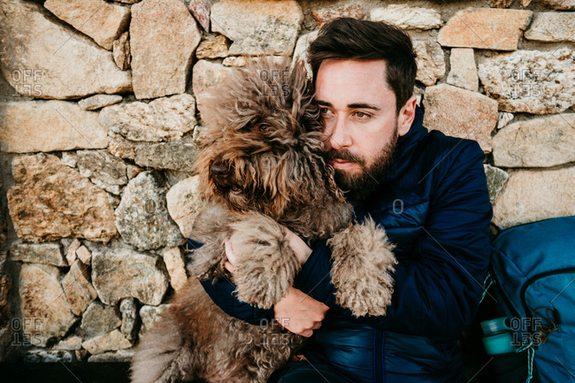 Bearded man embracing furry Labradoodle while sitting near stone wall of house during trip in Puerto de la Morcuera, Spain