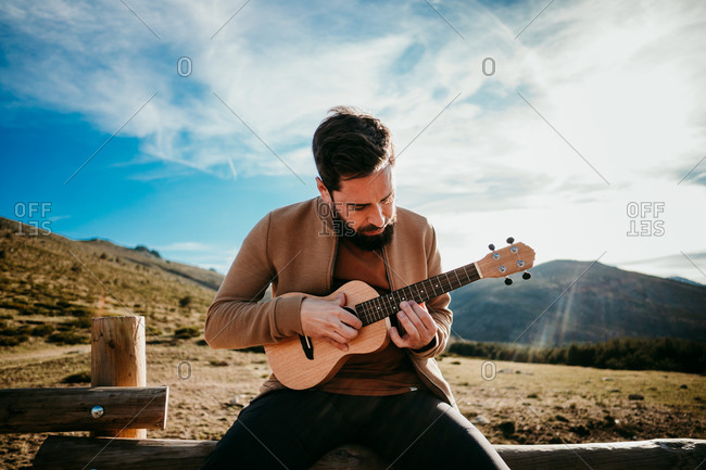 Serious bearded traveler sitting on fence against cloudy sky and playing ukulele on sunny day in Puerto de la Morcuera, Spain