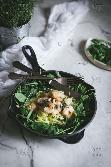From above portion of delicious zucchini noodles with boiled prawns and fresh spinach leaves placed on frying pan with fork and knife on marble table