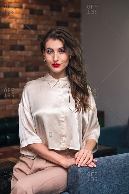 Charming confident young female with red lips and long wavy hair dressed in stylish blouse and pants looking at camera while sitting on chair in modern room with loft interior