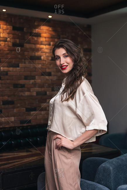Side view of charming confident young female with red lips and long wavy hair dressed in stylish blouse and pants looking at camera while standing near chair in modern room with loft interior