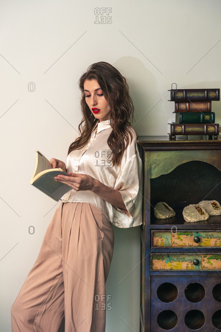 Side view of positive young female in stylish outfit leaning back on vintage cabinet and reading interesting book in cozy room