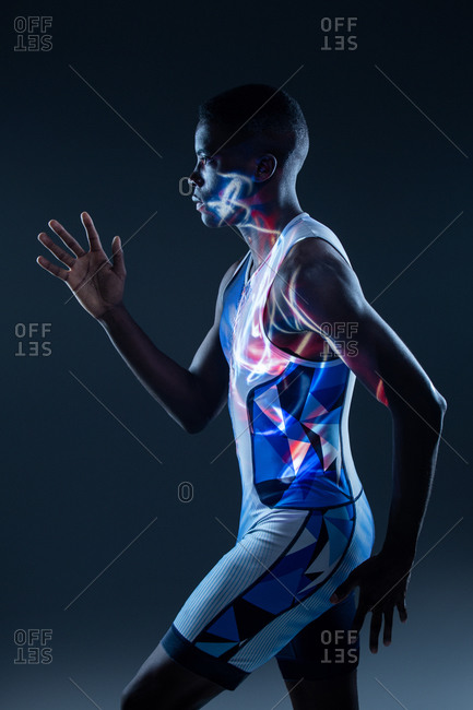 Side view of serious athletic African American sportsman in colorful active wear performing running fast movement in dark studio with red neon illumination