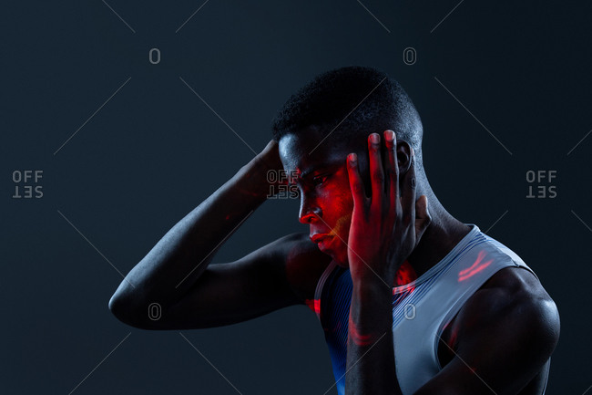 Side view of serious brutal African American athlete in sportswear keeping hands on head and looking away with challenge while standing in dark studio with red neon lights