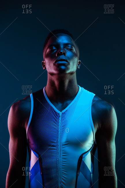 Serious concentrated young African American male athlete standing against blurred blue neon background in dark studio with eyes closed