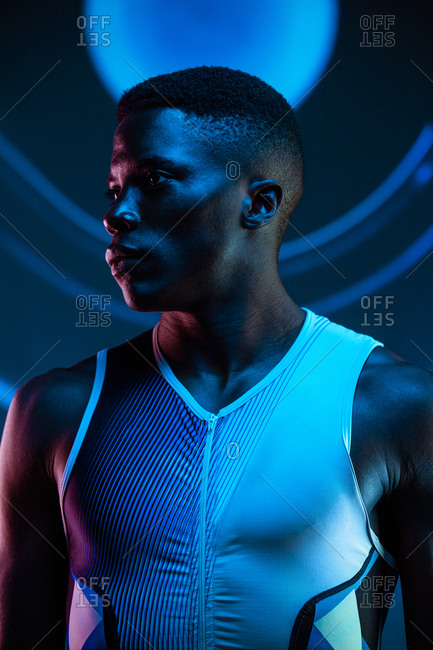 Serious concentrated young African American male athlete standing against blurred blue neon background in dark studio looking away