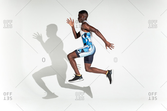 Full body side view of energetic young African American male sprinter jumping against white background