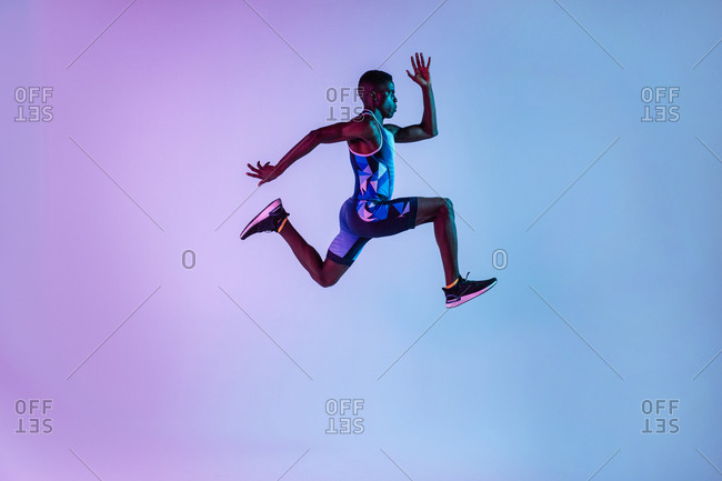 Full body side view of energetic young African American male sprinter jumping against blue neon background