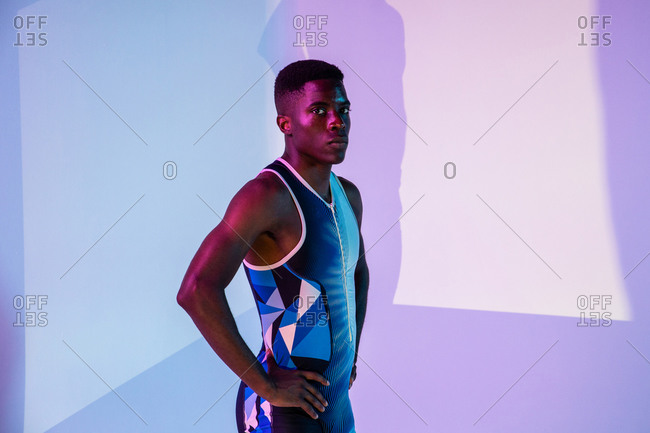 Full body side view of energetic young African American male sprinter standing against purple neon background looking at camera