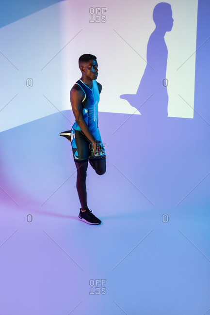 Side view of professional young African American sportsman in active wear performing stretching exercise during training in studio with colorful background and neon lights looking away