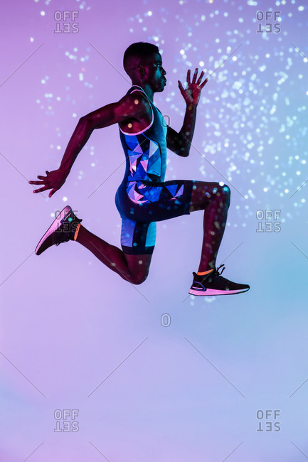 Full body side view of energetic young African American male sprinter jumping against blue and purple neon background