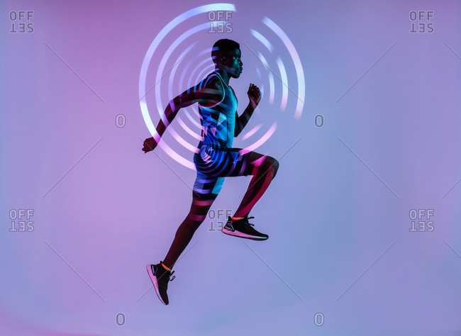 Side view of energetic young African American male sprinter jumping against purple wall with concentric circles in studio with neon lights neon background