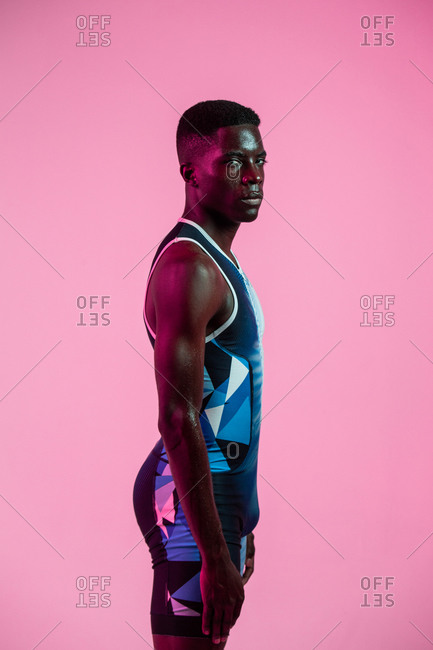 Side view of professional young African American sportsman in active wear standing during training in studio with colorful background looking at camera