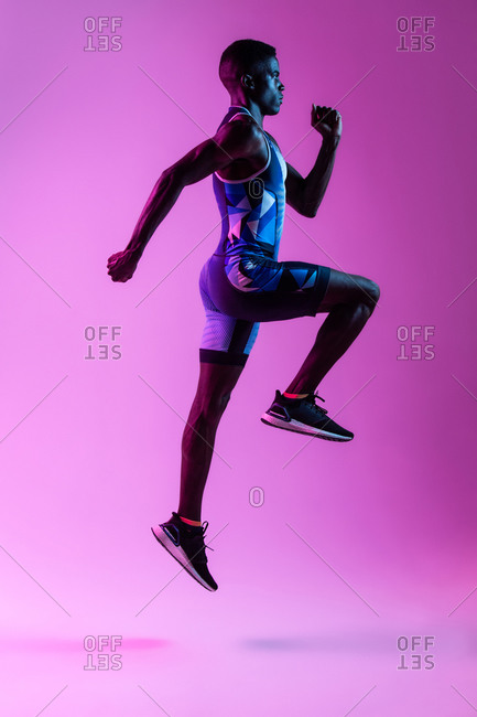 Full body side view of energetic young African American male sprinter jumping against purple neon background