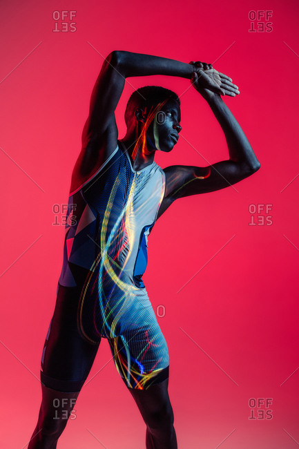 Professional young African American sportsman in active wear performing side bend exercise during training in studio with colorful background and neon lights