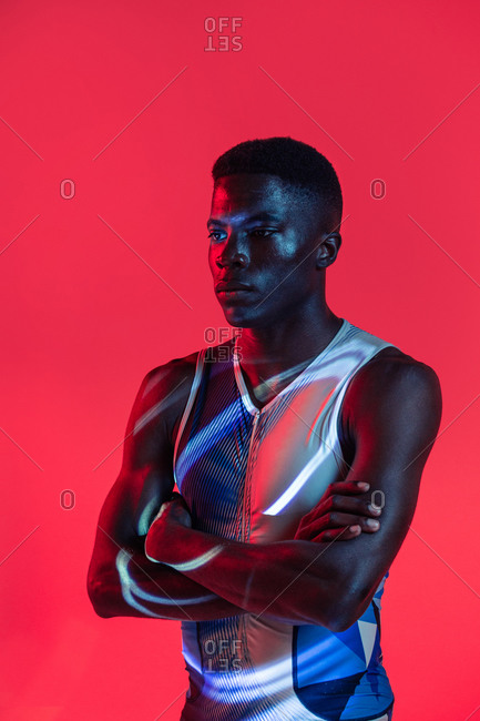 Side view of professional young African American sportsman in sportive outfit standing in studio with red neon illumination