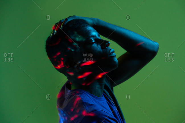 Serious confident young African American male with colorful neon lights on face with hand on head with eyes closed against green background