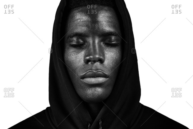 Black and white young African American male in hoodie with hood on head and closed eyes against white background